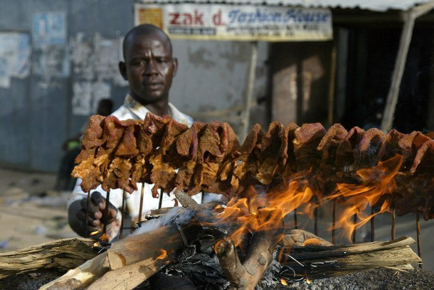 A man arranges sticks of meat on a mud platform for roasting in the ancient city of Kano 19 April, 2007. Roasted meat on sticks popularly known as 'Suya' is a common delicacy in northern Nigeria. AFP PHOTO PIUS UTOMI EKPEI (Photo credit should read PIUS UTOMI EKPEI/AFP/Getty Images)